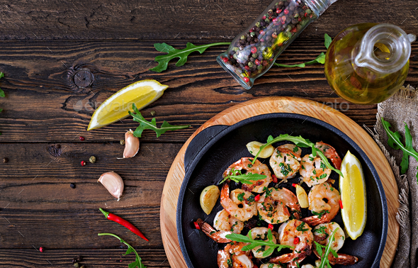 Prawns Shrimps roasted in garlic butter with lemon and parsley on wooden background.  - Stock Photo - Images