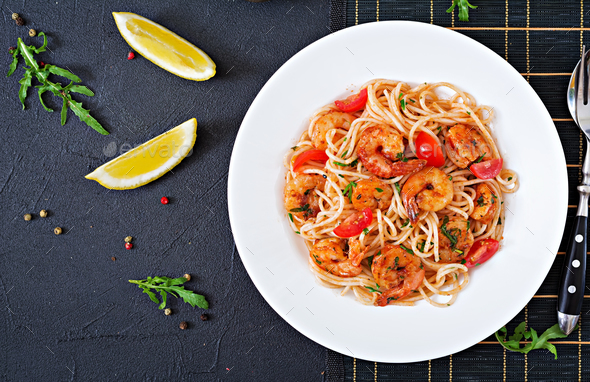 Pasta spaghetti with shrimps, tomato and parsley. Healthy meal. Italian food. Top view. Flat lay - Stock Photo - Images