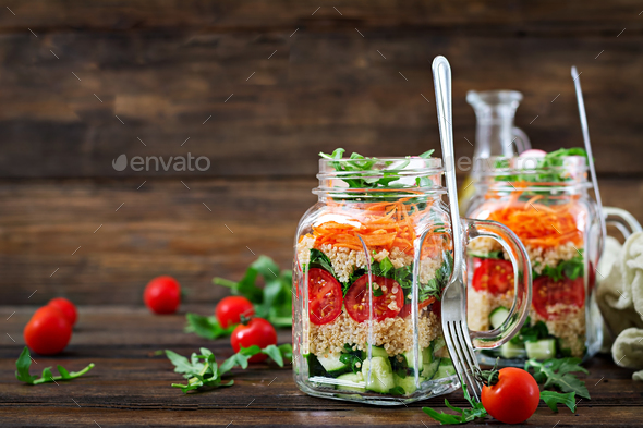 Salads with quinoa,  arugula, radish, tomatoes and cucumber in glass  jars on  wooden background.  - Stock Photo - Images