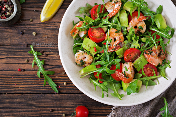 Fresh salad bowl with shrimp, tomato, avocado and arugula on wooden background close up.  - Stock Photo - Images