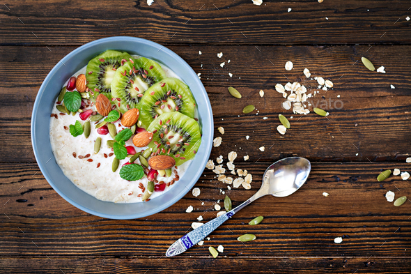 Healthy breakfast. Oatmeal with kiwi, pomegranate, flax seeds and nuts. Detox menu. Top view. - Stock Photo - Images