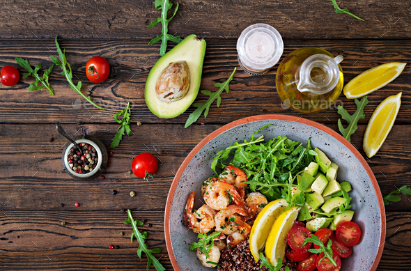 Buddha bowl with shrimps, tomato, avocado, quinoa, lemon and arugula - Stock Photo - Images