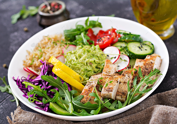 Buddha bowl lunch with grilled chicken and quinoa, tomato, guacamole, red cabbage, cucumber  - Stock Photo - Images