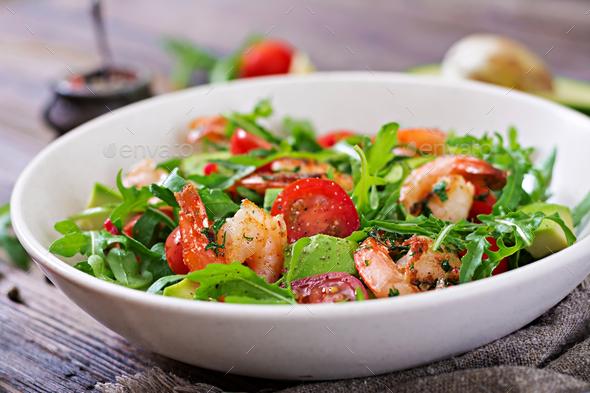Fresh salad bowl with shrimp, tomato, avocado and arugula on wooden background close up - Stock Photo - Images
