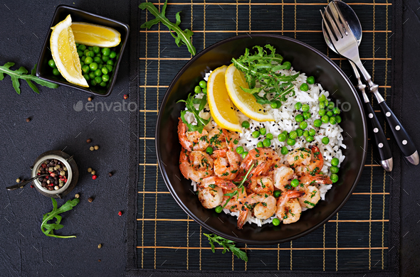 Rice with young green peas, shrimps and arugula in black bowl. Healthy food. Buddha bowl.  - Stock Photo - Images