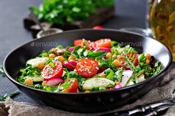 Salad of chickpeas, tomatoes, cucumbers, radish and greens. Dietary food. Vegan salad. - Stock Photo - Images