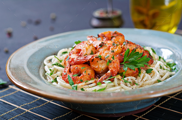 Pasta spaghetti with shrimps, tomato and chopped parsley. Healthy food. Italian meal. - Stock Photo - Images