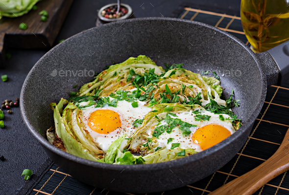 Fried eggs with slices of young cabbage and greens. Nutritious breakfast. - Stock Photo - Images