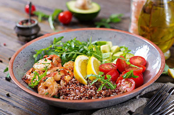 Buddha bowl with shrimps, tomato, avocado, quinoa, lemon and arugula on the wooden table. - Stock Photo - Images