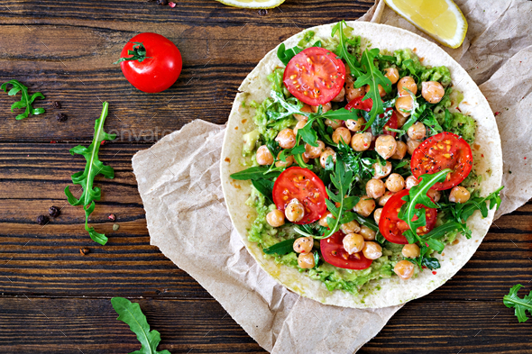Vegan tacos with guacamole, chickpeas, tomatoes and arugula.  - Stock Photo - Images