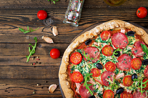 Pizza with salami, tomatoes, olives and cheese on a dough with whole wheat flour - Stock Photo - Images