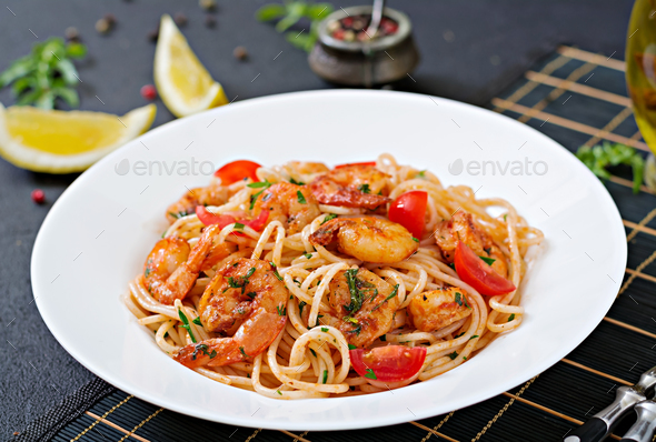 Pasta spaghetti with shrimps, tomato and parsley. Healthy meal. Italian food. - Stock Photo - Images