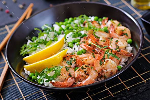 Rice with young green peas, shrimps and arugula in black bowl. Healthy food. Buddha bowl - Stock Photo - Images