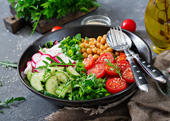 Salad of chickpeas, tomatoes, cucumbers, radish and greens. Dietary food. Vegan salad. - Stock Photo - Images