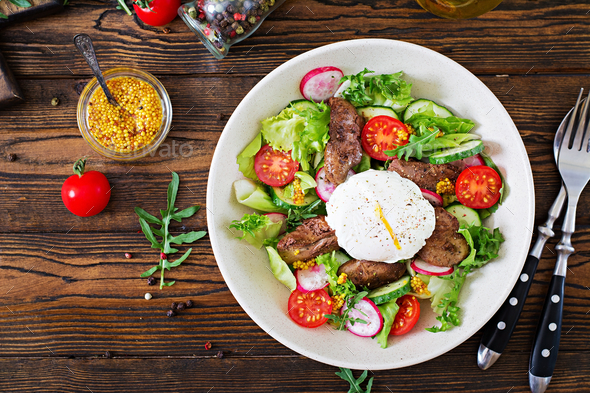Warm salad from chicken liver, radish, cucumber, tomato and egg poached - Stock Photo - Images