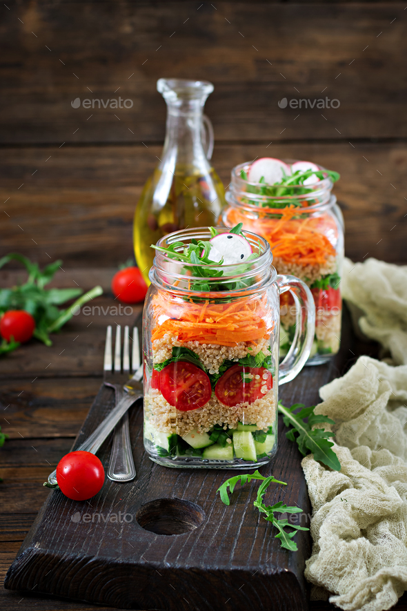 Salads with quinoa,  arugula, radish, tomatoes and cucumber in glass  jars  - Stock Photo - Images