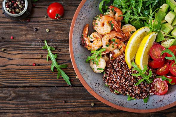 Buddha bowl with shrimps, tomato, avocado, quinoa, lemon and arugula - Stock Photo - Images