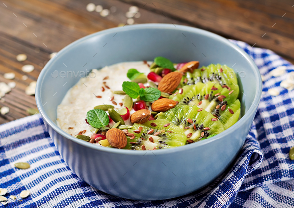 Healthy breakfast. Oatmeal with kiwi, pomegranate, flax seeds and nuts. Detox menu. - Stock Photo - Images