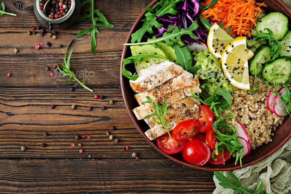 Buddha bowl lunch with grilled chicken and quinoa, tomato, guacamole, carrot, red cabbage, cucumber - Stock Photo - Images