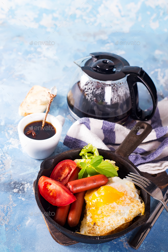 Homemade delicious breakfast on a pan with fried egg, toast, sausage, vegetable, black coffee - Stock Photo - Images