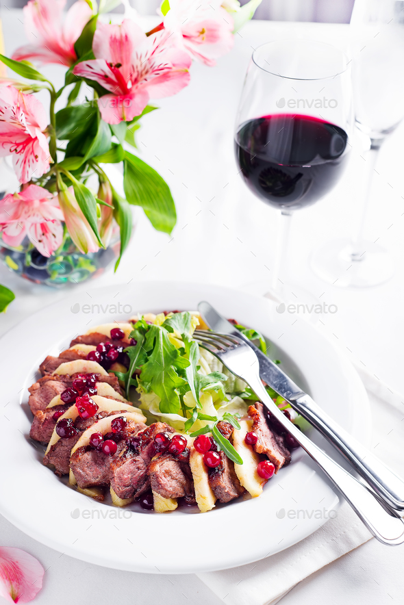 Salad with slices of duck breast with apples and salad under cowberry sauce - Stock Photo - Images