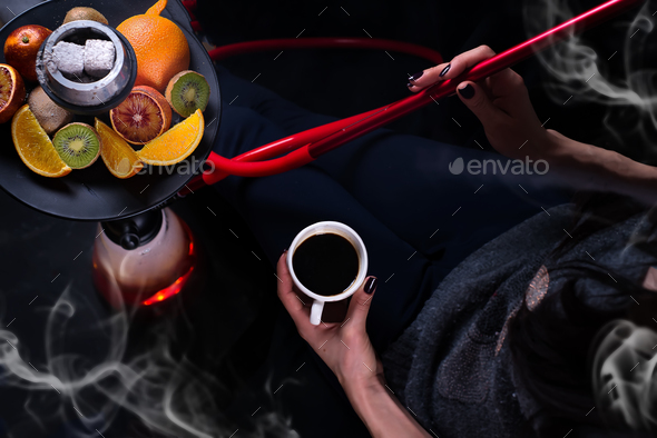 A girl with a cup of coffee in her hands smokes a hookah - Stock Photo - Images