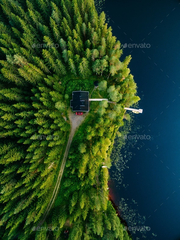 Aerial view of wooden cottage in green forest by the blue lake in rural summer Finland - Stock Photo - Images