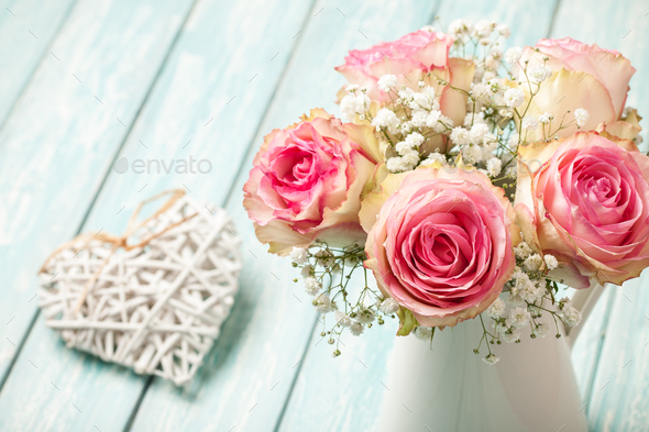 Pink roses in jug and heart decoration on blue background - Stock Photo - Images