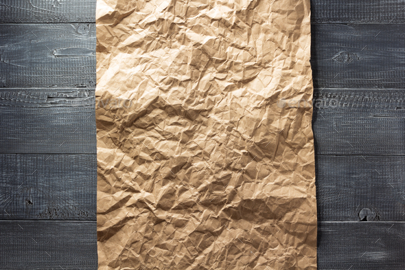 wrinkled paper at wood - Stock Photo - Images