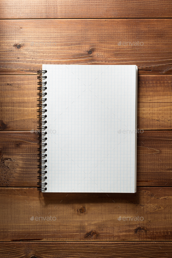 checked notebook on wooden background - Stock Photo - Images