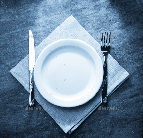 plate, knife and fork on napkin - Stock Photo - Images