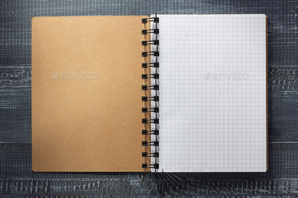 checked notebook at wooden  background - Stock Photo - Images