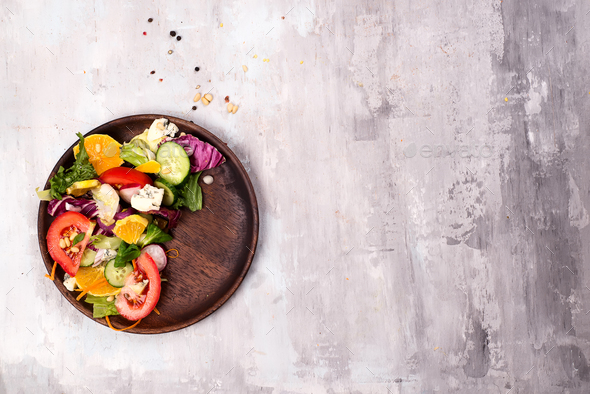 Healthy salad with fresh vegetables and souse in wooden plate - Stock Photo - Images