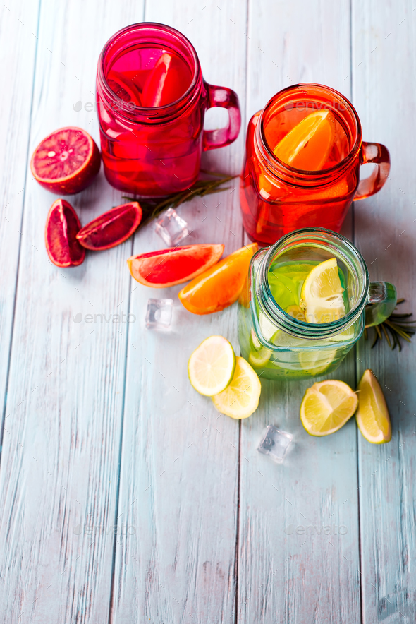 three colored glasses with citrus lemonade and a slice of fruit on a blue background - Stock Photo - Images