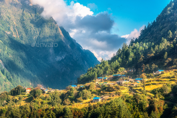 Small village on the hill lighted by a sunbeam against mountains - Stock Photo - Images