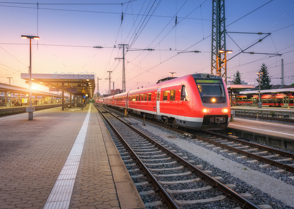 Passenger high speed train on the railway station at sunset - Stock Photo - Images