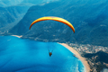 Paraglider tandem flying over the sea with blue water and mountains - PhotoDune Item for Sale