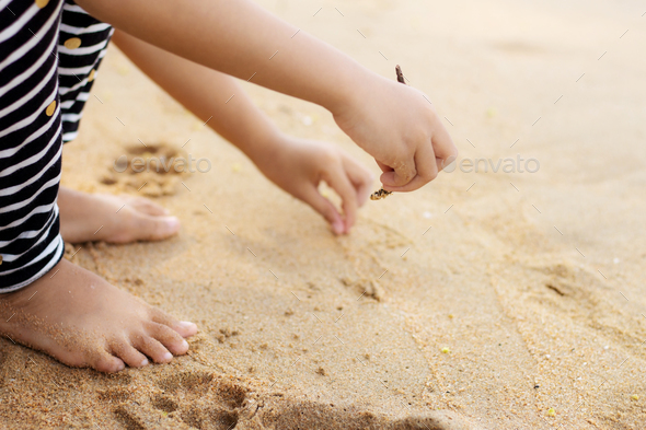 Girl on sand and writing - Stock Photo - Images