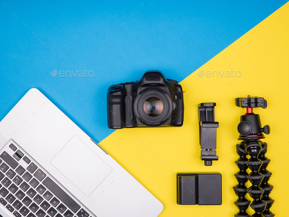 Camera with accessories next to a laptop - Stock Photo - Images