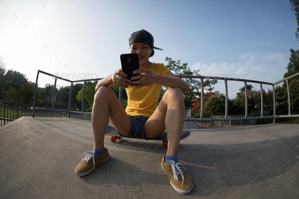 Female skateboarder using mobile phone at skatepark - Stock Photo - Images