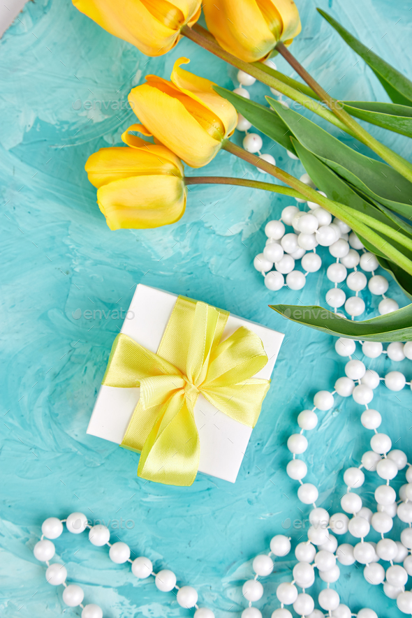 Gift box with yellow ribbon near tulip - Stock Photo - Images
