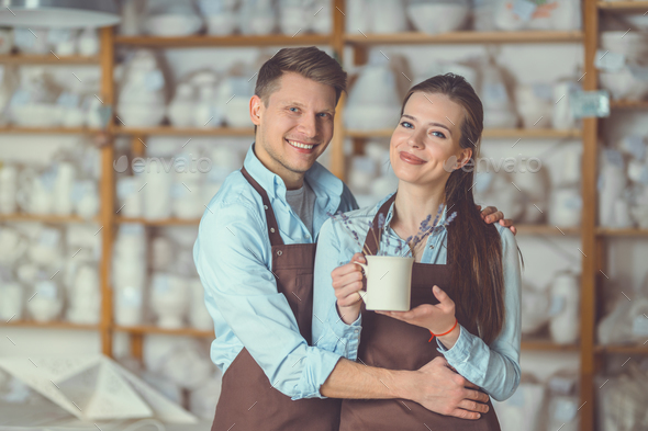 Smiling couple with a ceramic vase - Stock Photo - Images