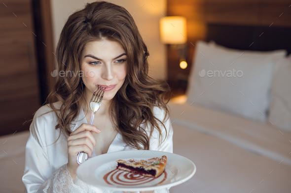 Attractive girl eating breakfast in the hotel - Stock Photo - Images