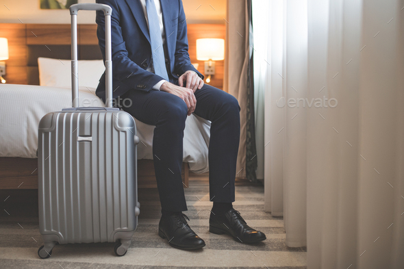 Young businessman in suit with a suitcase - Stock Photo - Images