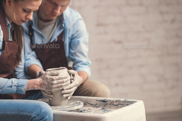 Young couple at the potter's wheel - Stock Photo - Images