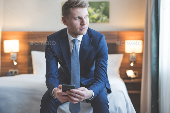 Young businessman with a phone in room - Stock Photo - Images