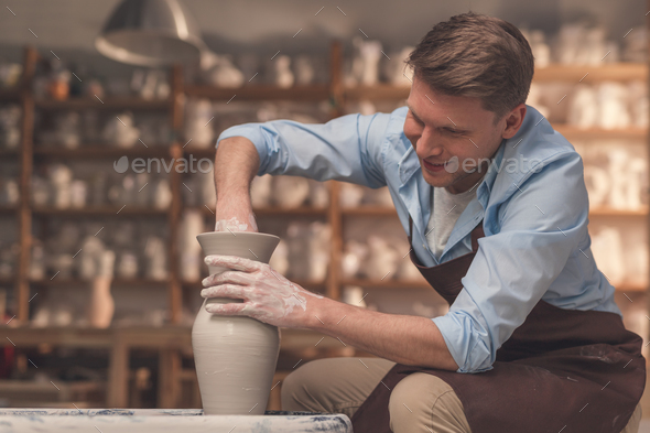 Young man at the potter's wheel - Stock Photo - Images