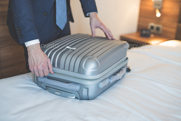 Young businessman with a luggage in the room - Stock Photo - Images