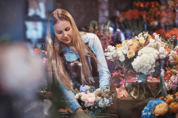 Attractive girl in uniforn in a flower shop - Stock Photo - Images