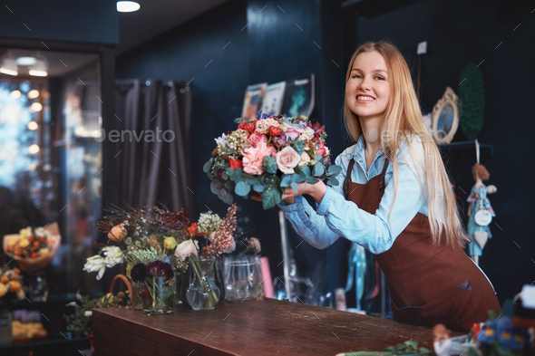 Smiling girl in a flower shop - Stock Photo - Images